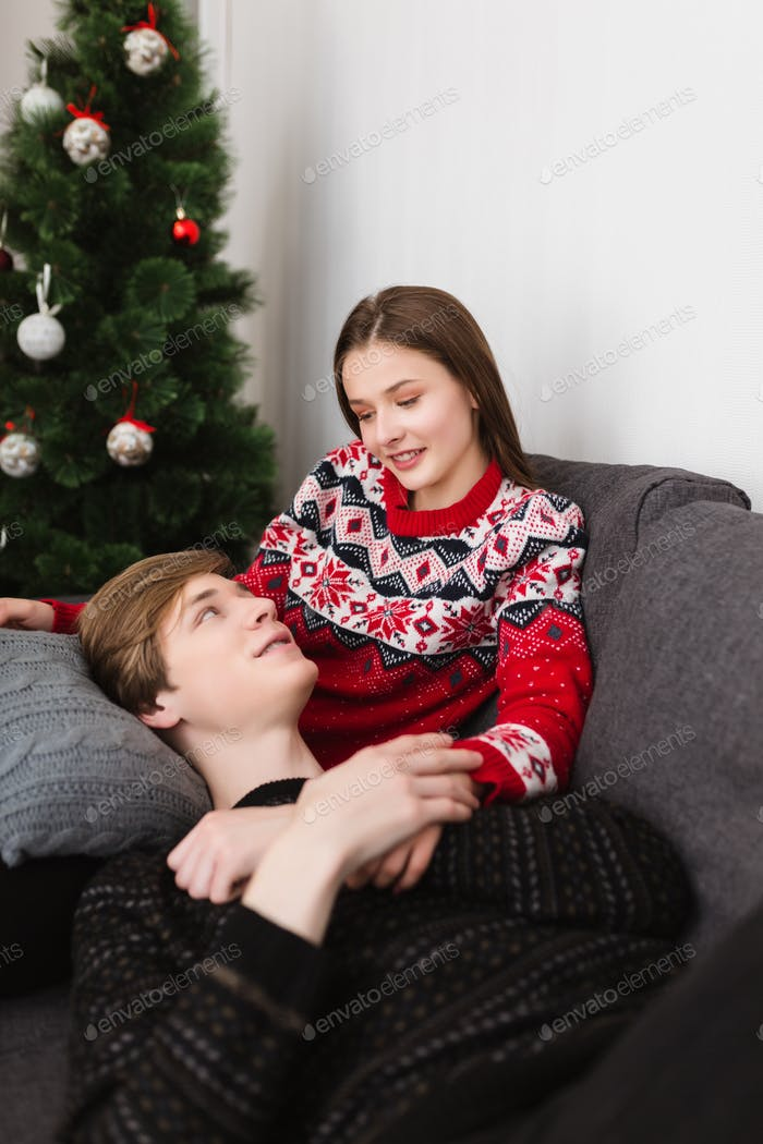 Lächelnd junges Paar liegend auf Sofa zu Hause zusammen träumig suchen einander