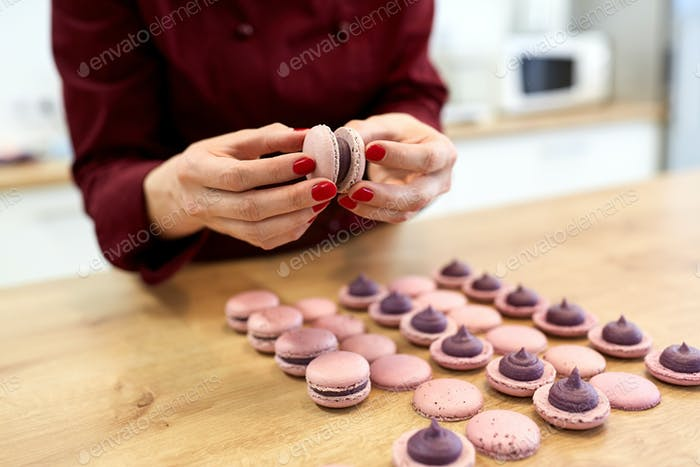 chef sandwiching macarons shells with cream