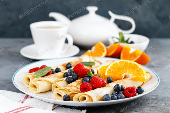 Sweet pancakes wrapped with fresh berries, crepes with blueberry and raspberry for breakfast