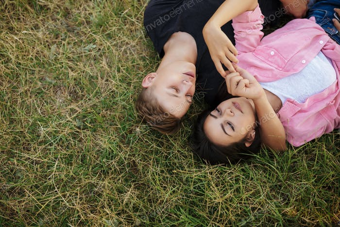 Young beautiful couple lying on green lawn while spending time together in park