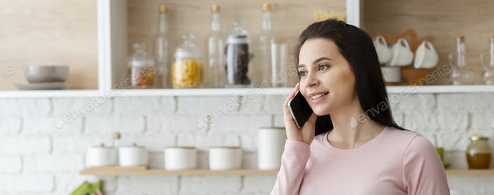 Young woman talking on cellphone at kitchen interior