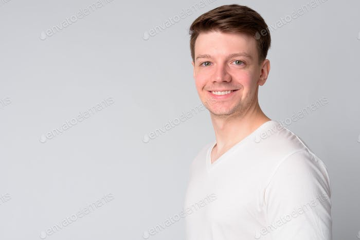 Profile view of happy young handsome man looking at camera