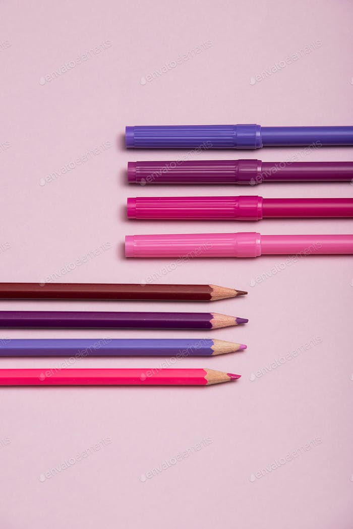 Colourful pencils over a pink background