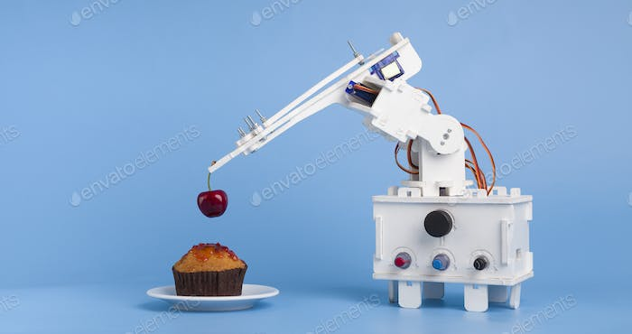 Robot cooking dessert, decorating sweet cupcake with fresh cherry