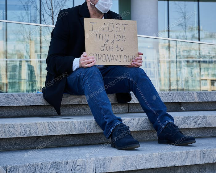 "Job loss due to COVID-19 virus pandemic concept. Unrecognizable man holds sign ""I lost my job"""