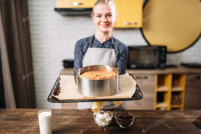 Woman cook in apron holds pan with fresh cake