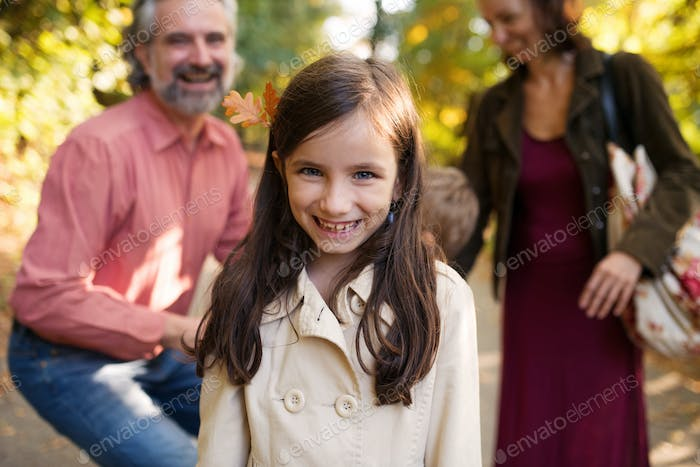 Small girl with family on a walk in autumn forest