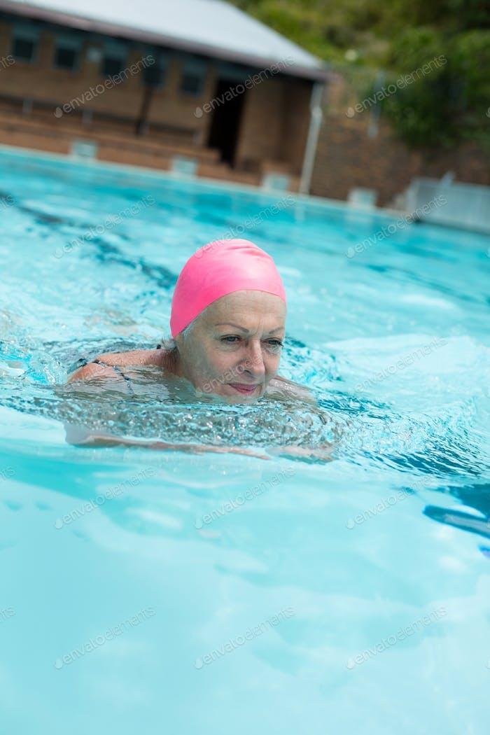 Senior woman wearing cap while swimming in pool