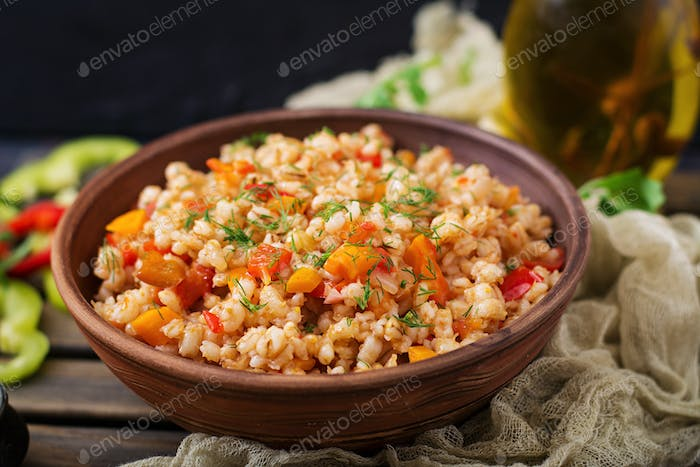 Vegetarian crumbly pearl barley porridge with vegetables  in a dark background