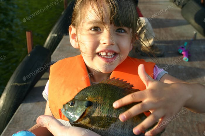 Happy Little Girl Shows Off the First Fish She Caught