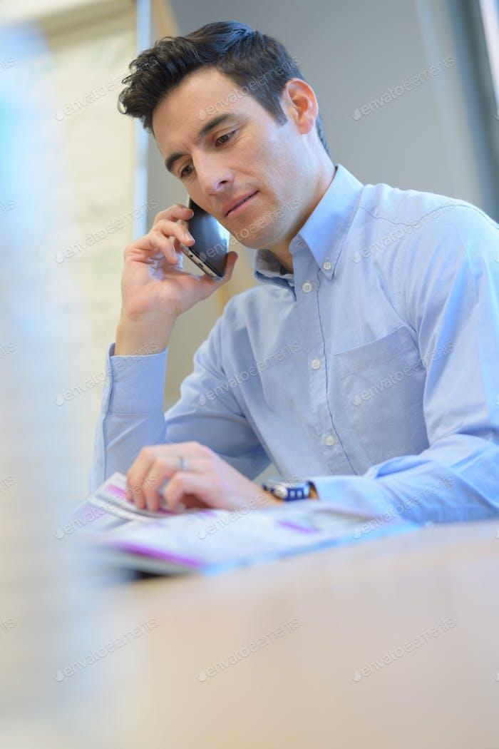 Geschäftsmann sitzt am Tisch und mit Smartphone im Büro