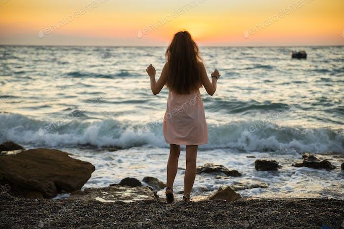 Mujer joven en vestido de verano en el Fondo de la puesta de sol en el Mar