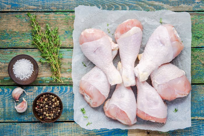raw organic chicken legs on paper with thyme, salt and pepper