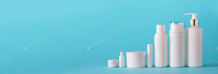White cosmetic tubes on blue background with copy space. Skin care, body treatment, beauty concept