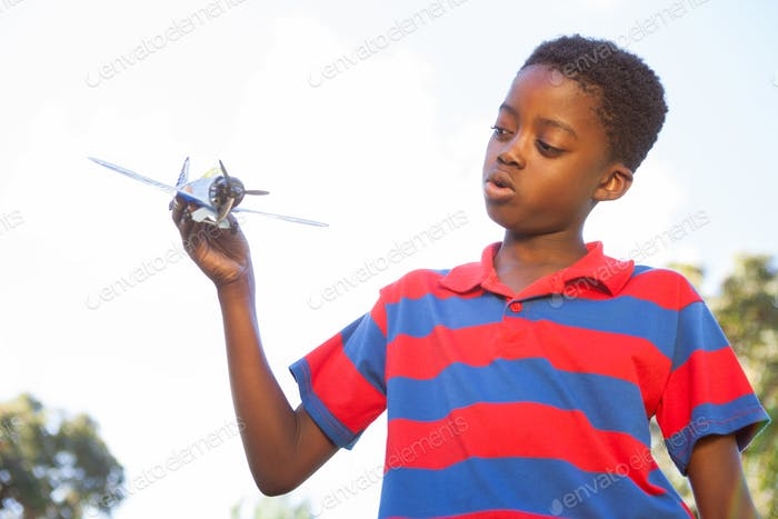Little boy playing with toy airplane on a sunny day
