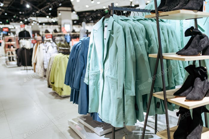 Clothes, coats on racks in clothing store, nobody