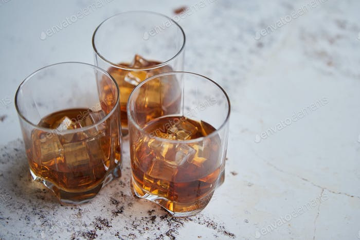 Three glasses filled with ice cubes and old aromatic whiskey