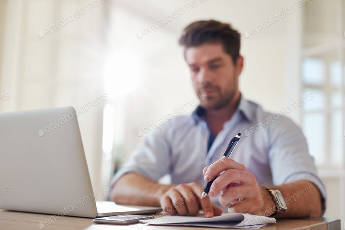 Businessman at home office taking notes