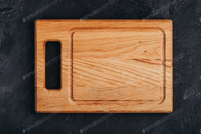 Empty Wooden Chopping or Cutting  Board on dark stone concrete background