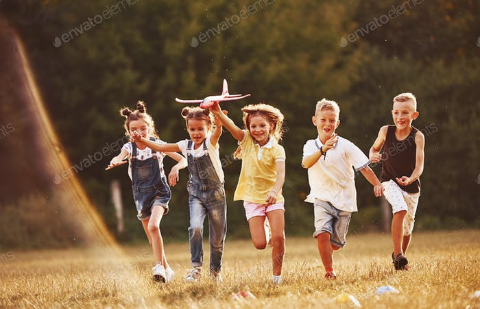 Group of kids having fun outdoors with red toy airplane in hands
