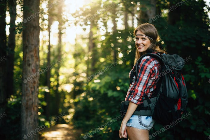 Beautiful woman hiking in forest