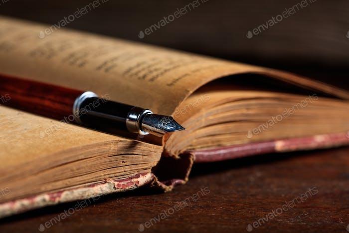 Vintage-Buch und Tintenschreiber auf einem Holzschreibtisch