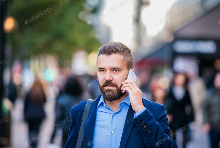 Hipster manager with smart phone walking in the street
