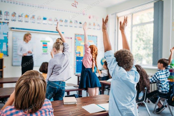 kids raising hands in class to answer teachers question
