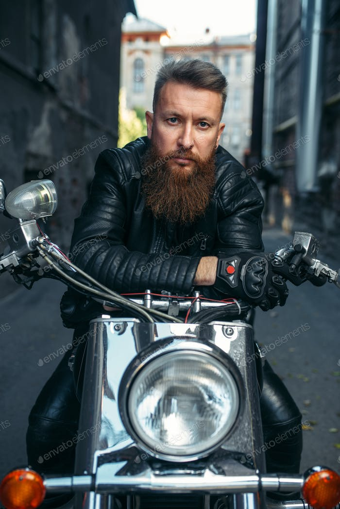 Bearded biker on classical chopper, front view
