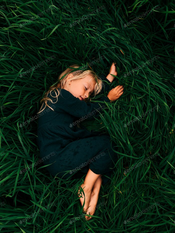 Sea of Grass - Little Girl Laying on a Filed of Grass
