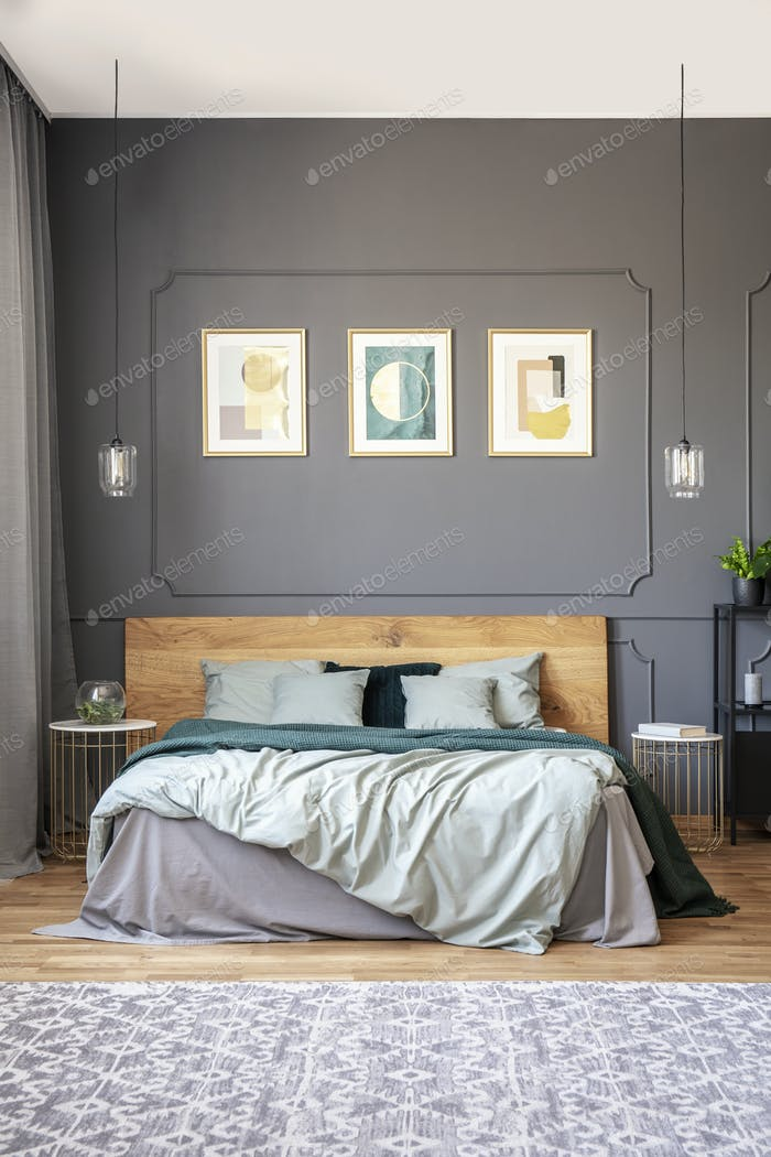 Posters on grey wall with molding above wooden bed in modern bed