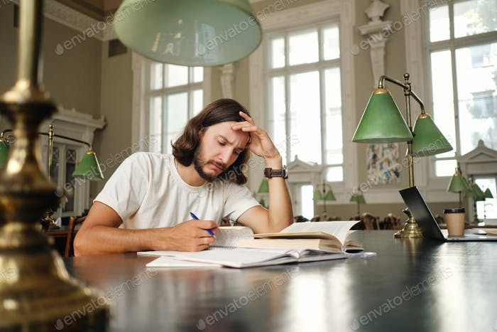 Tired student thoughtfully preparing to exam with book and study notes in library of university