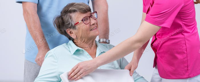 Nurse covering senior by blanket
