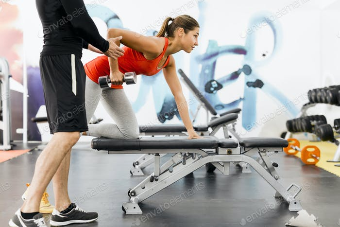 Young male trainer giving instructions to a woman in a gym