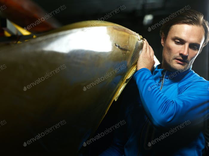 Young concentrated Caucasian sportsman in blue swimming jacket carrying boat