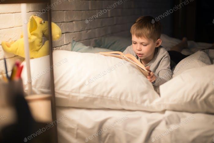 Cute Little Boy Lesbuch bei Nacht