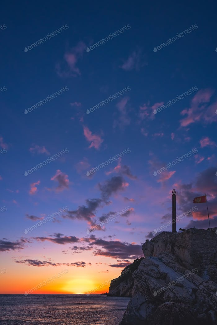 Obelisk and flag on the cliffs at dusk