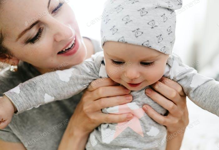 Glückliche lächelnde Mutter und Baby spielen auf dem Bett zu Hause. Glückliche Familie, die Spaß hat.