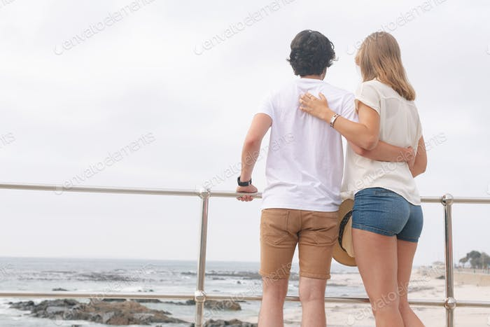 Young Caucasian couple standing on the promenade at the seaside.