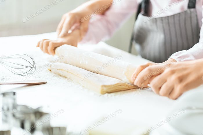 Girl and her mom rolling out dough on kitchen table