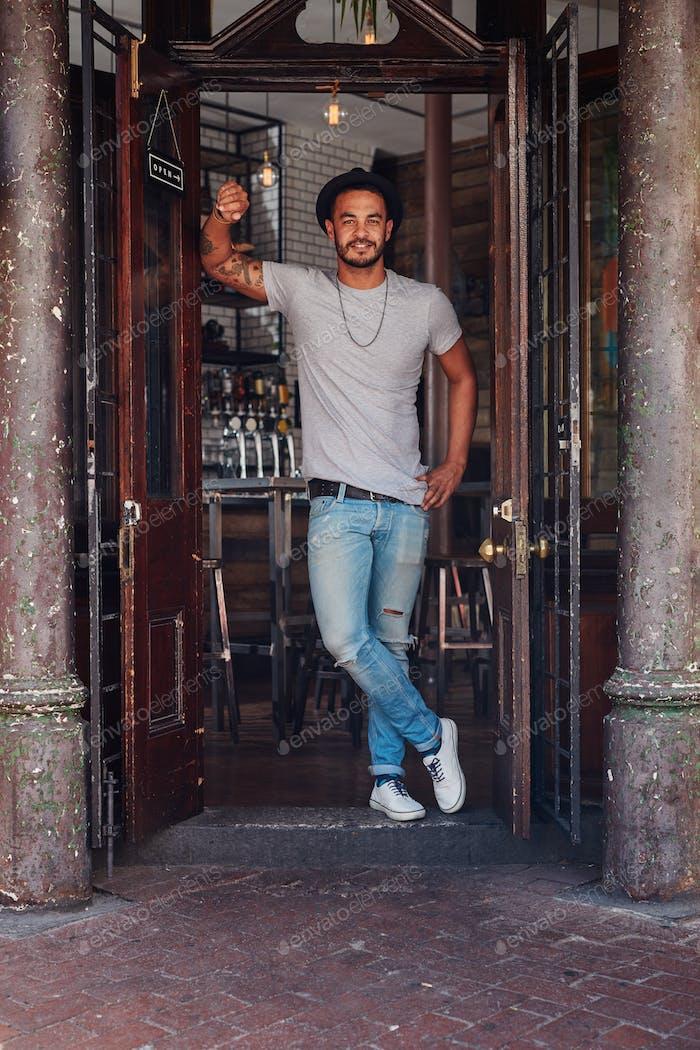 Современный молодой парень, стоящий у входа в кафе