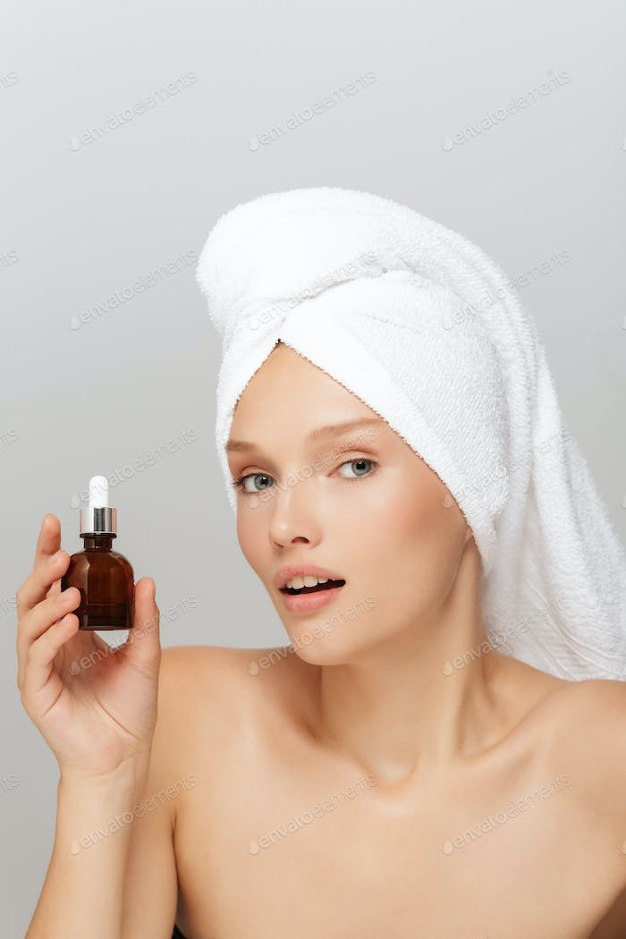Portrait of young lady without makeup with white towel on head h