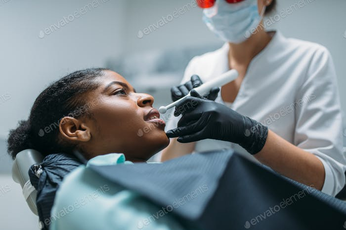 Dentist installs the seal on tooth, dental clinic