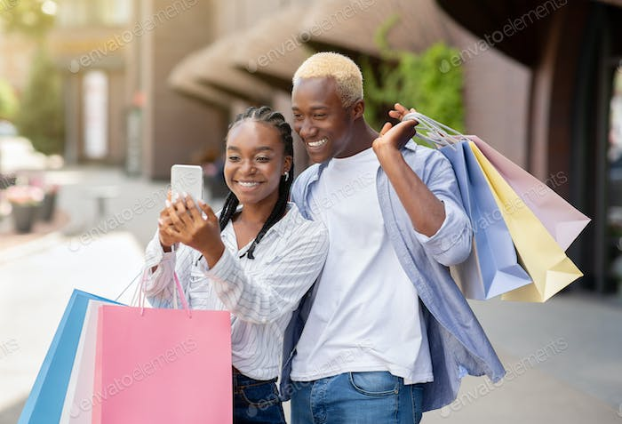 Bonuses, gifts and cashback after shopping. Happy couple with many color bags looks at smartphone