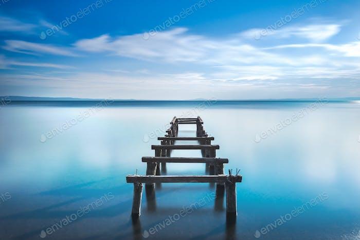 Hölzerne Pier oder Steg bleibt auf einem blauen See. Lange Belichtung.