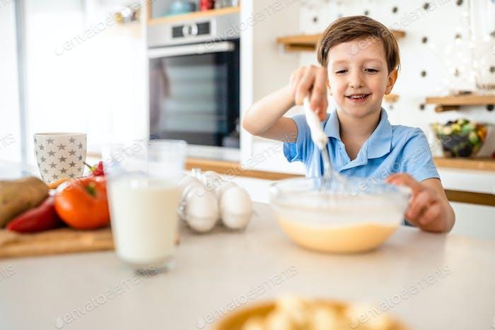 Happy beautiful kid learn preparing breakfast at home kitchen