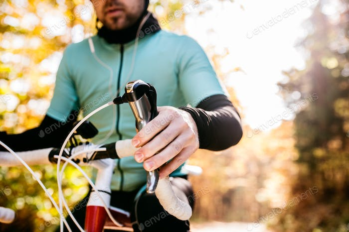 Unrecognizable sportsman riding his bicycle in sunny autumn natu