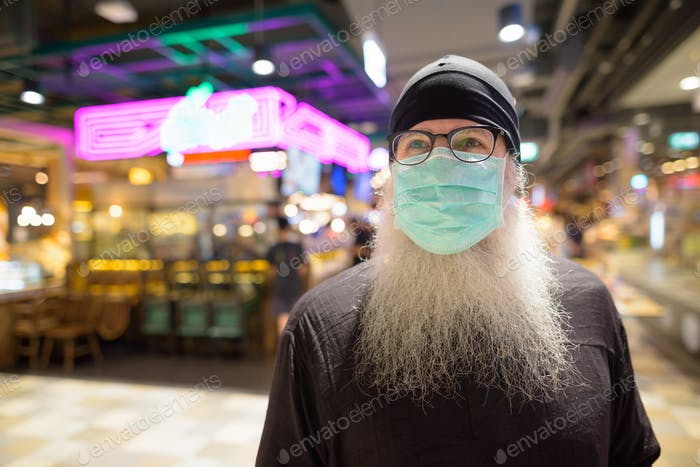 Mature bearded hipster man thinking with mask for protection from corona virus outbreak at the mall