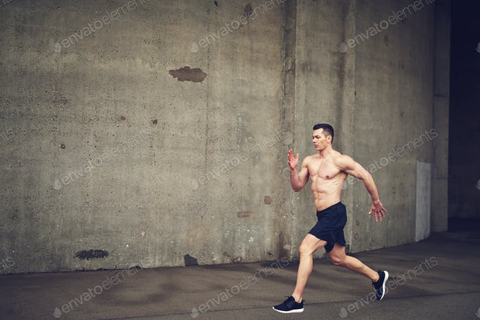 Shirtless young male running against concrete wall