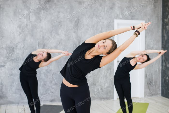 Smiling yogi girl in class in Yoga asana, exercising, stretching